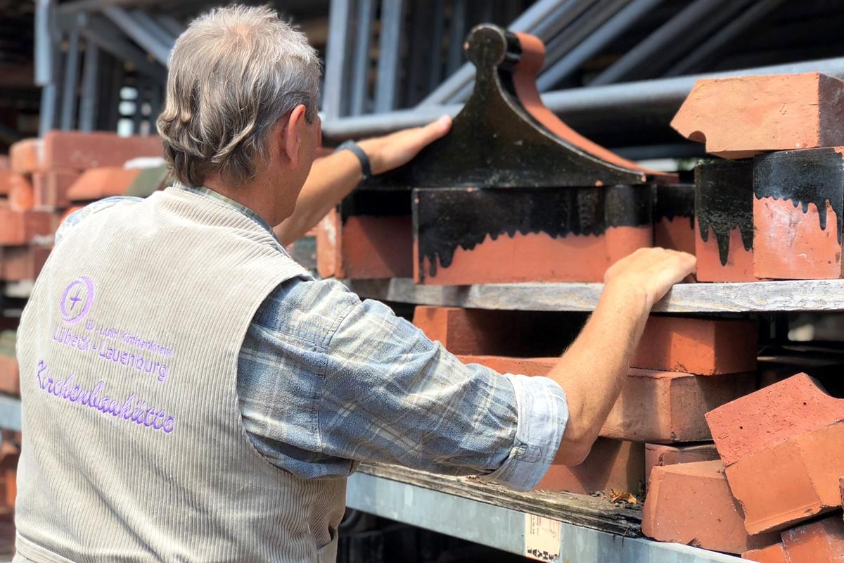 Ein Bauregal mit verschiedenen Backsteinen- Links im Bild die Rückansicht eines Mannes.
