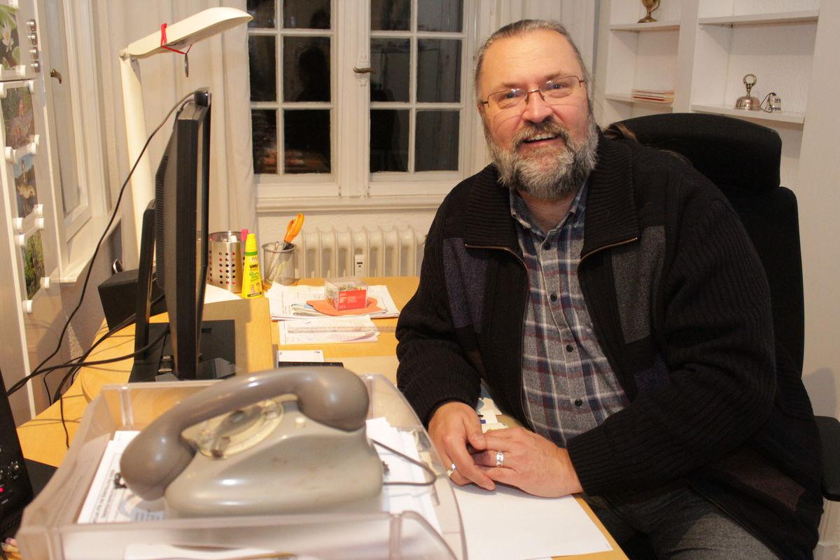 Ein Mann mit grau meliertem Bart, hoher Stirn und unauffälliger Brille sitzt an einem Schreibtisch und lächelt in die Kamera. Im Vordergrund steht in einem Eingangskorb ein graues Wählscheibentelefon.