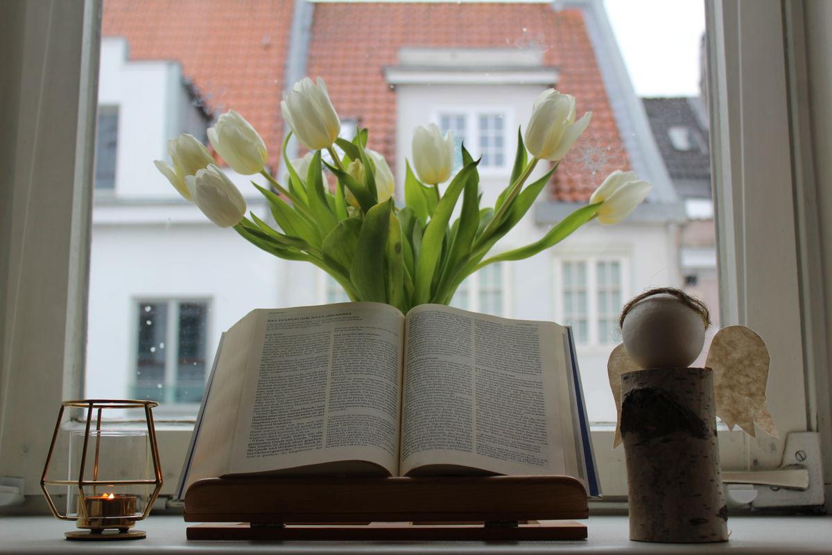Auf einem Ständer liegt eine aufgeschlagene Bibel, rechts eine Engelsfigur, links eine kleine Kerze. Dahinter steht ein Strauß weißer Tulpen. Im Hintergrund sieht man durch ein Fenster auf andere Häuser.