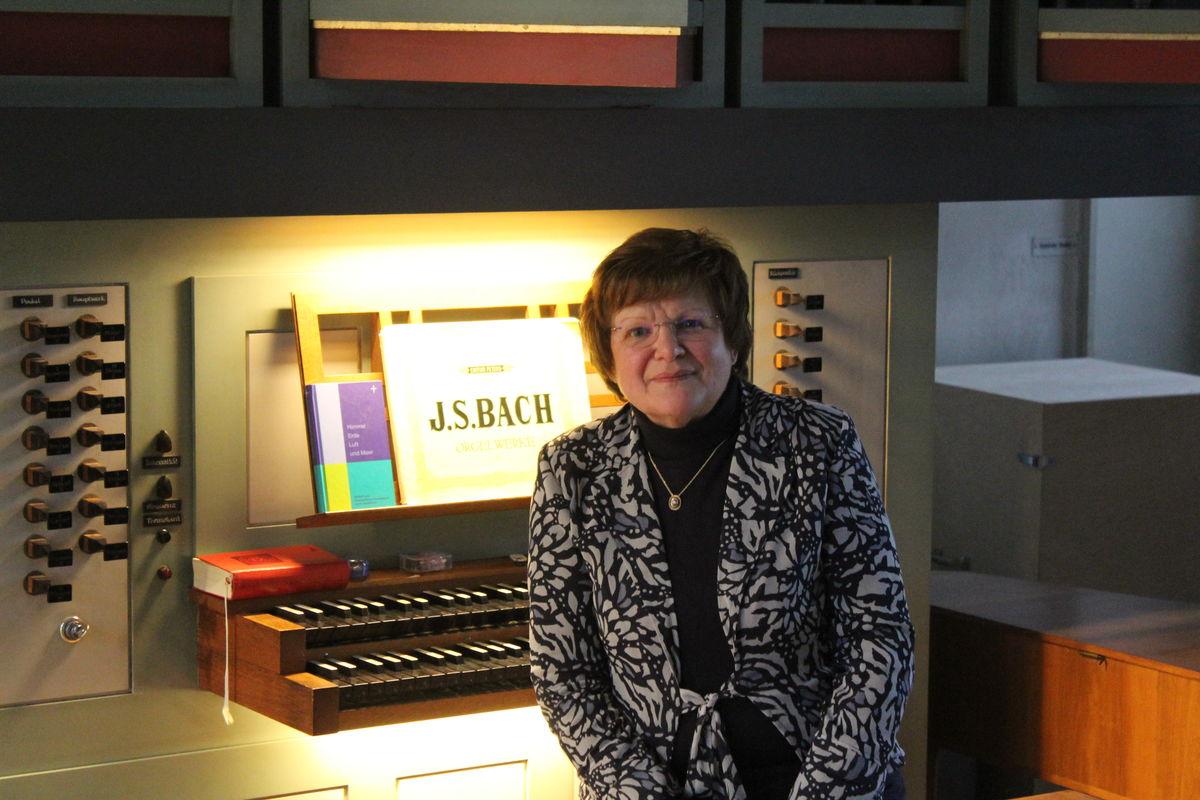 Eine Frau mit dunklen, kurzen Haaren sitzt an einem Orgelspieltisch und blickt freundlich in die Kamera. Auf dem Notenpult liegt ein Notenheft von Johann Sebastian Bach.