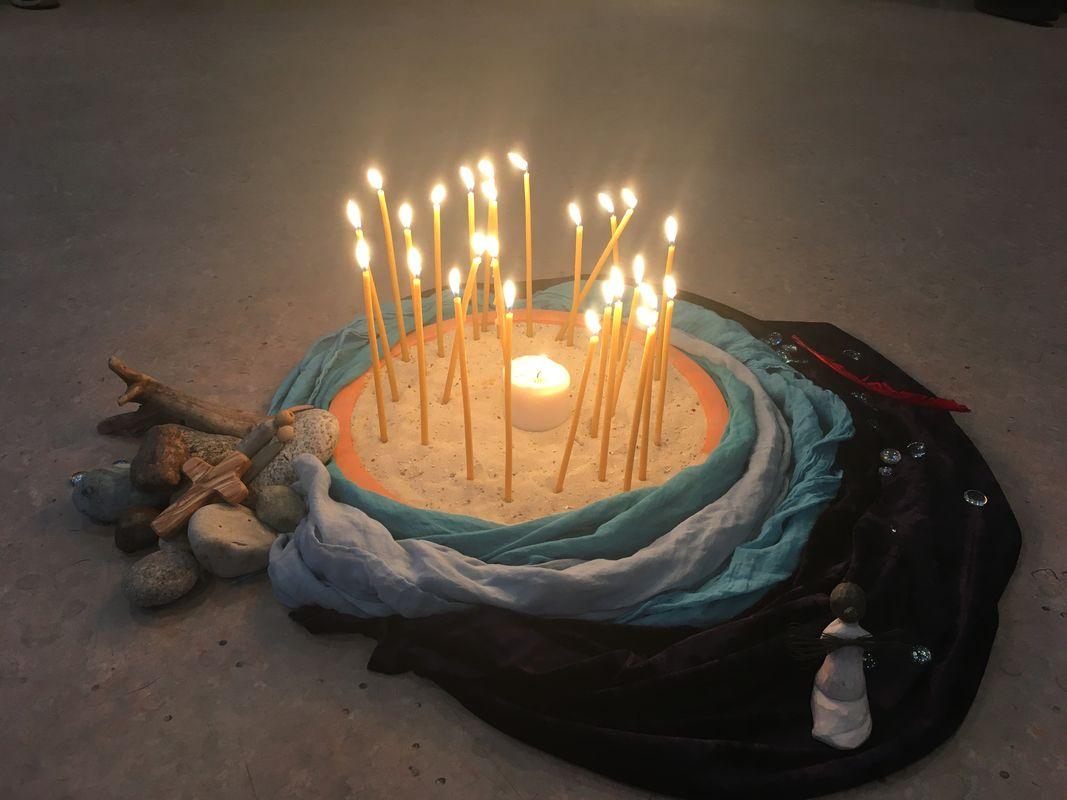 Auf einem sandigen Untergrund ist ein Kreis aus Tüchern gelegt. Darin stehen brennende Kerzen. An der Seite liegen Steine, ein Holzkreuz und Figuren.