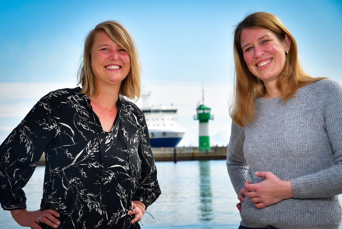 Zwei Frauen blicken freundlich in die Kamera, im Hintergrund die die Nordermole in Travemünde: Grün-weißer Leuchtturm, der Bug eines Containerschiffs