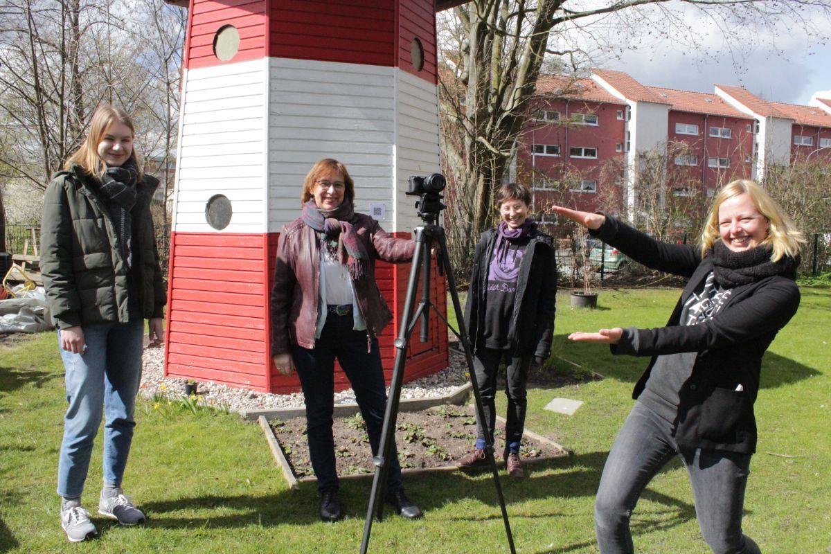"""Die Macher hinter der Video-Reihe """"Luther aus dem Häuschen"""" vor dem bekannten Leuchtturm der Luther-Melanchthon-Gemeinde in Lübeck."""
