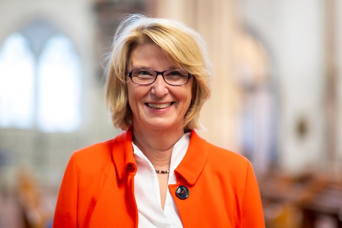 Eine Frau im Portrait. Sie trägt eine weiße Bluse, darüber eine Jacke in orange.