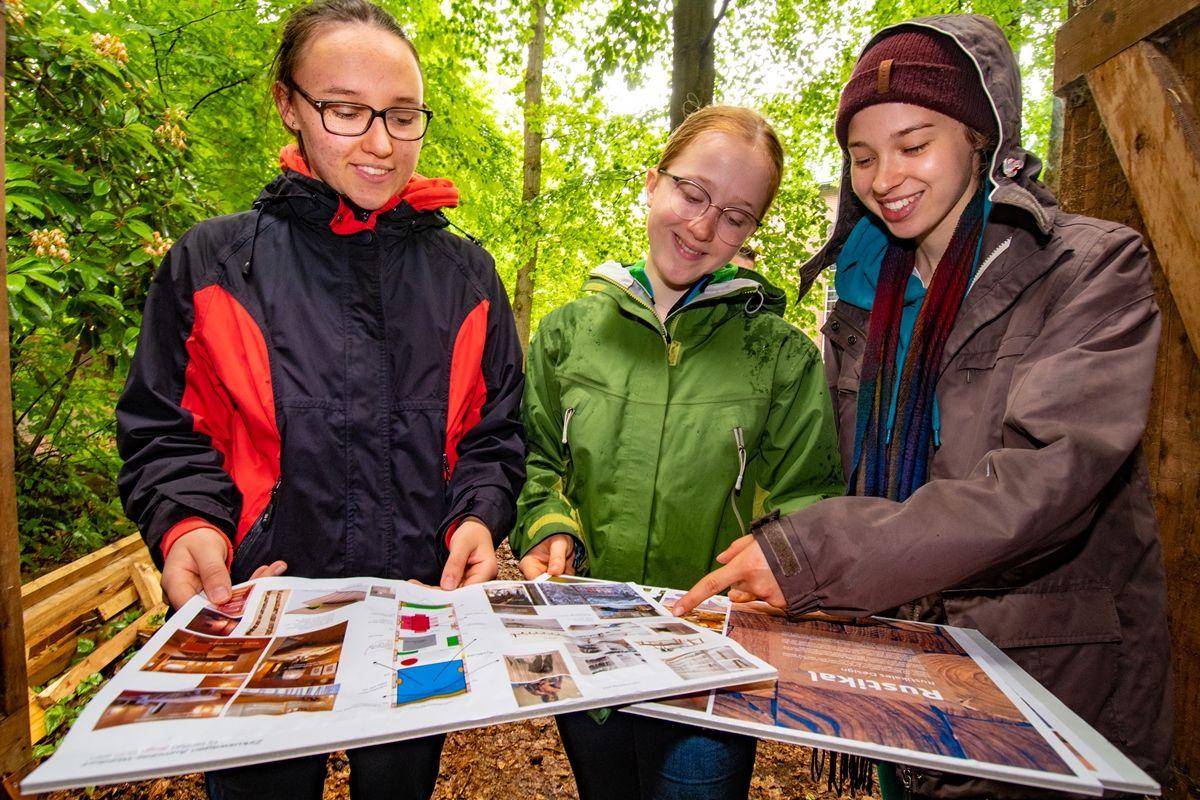 Drei junge Frauen schauen sich Pläne und Fotos an. Sie stehen im freien, unter grünen Bäumen.