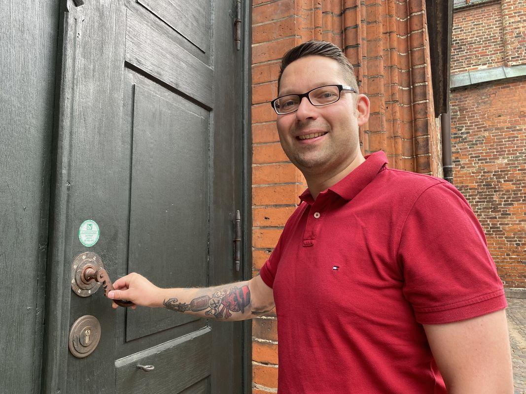 Mann im roten T-Shirt öffnet eine Kirchentür