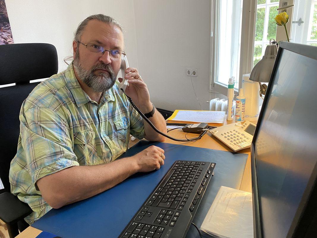 Mann in kariertem Hemd sitzt am Schreibtisch und telefoniert.