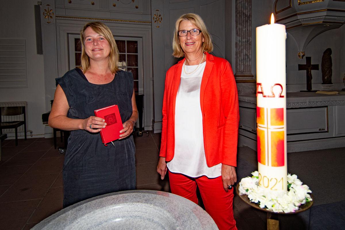 Zwei Frauen stehen an einem Taufbecken neben einer Kerze in einer Kirche.