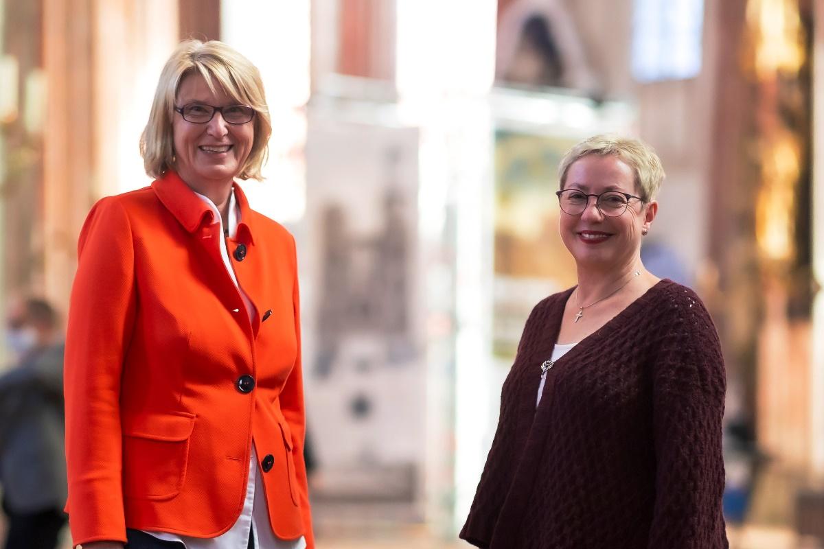 Zwei Frauen im Halbportrait schauen freundlich in die Kamera. Sie sind einander zugewandt, im Hintergrund ist unscharf der Kirchraum von St. Marien zu erkennen.