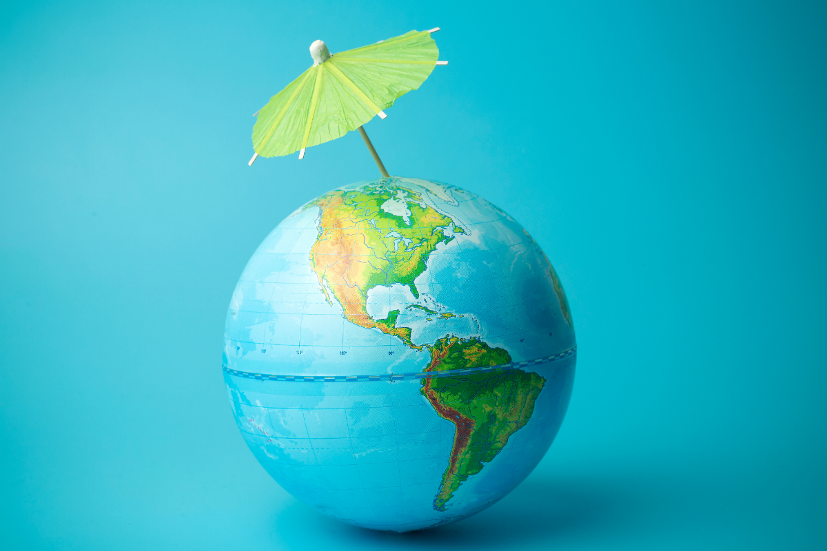 Eine Weltkugel mit Nord- und Südamerika. Ein kleines Papierschirmchen steckt aufgespannt im Nordpol.