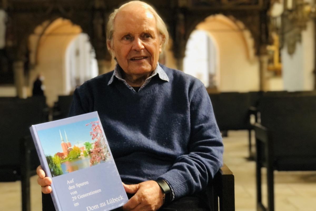 Gustav Querfurth mit seinem neuen Buch im Dom zu Lübeck.