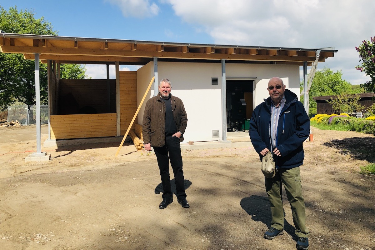 Michael Eggers (li.) und Olaf Dey vor dem Heizhaus. Im Herbst soll es in Betrieb gehen.