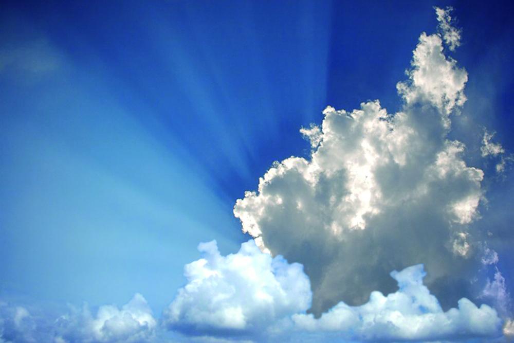Eine Wolke bedeckt die Sonne am blauen Himmel, aber man sieht die hellen Lichtstrahlen der Sonne