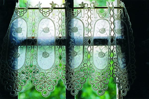 Ein Fenster mit Gardine und Blick Richtung Helligkeit und verschwommenen grünem Garten symbolisiert den Ewigkeitssonntag