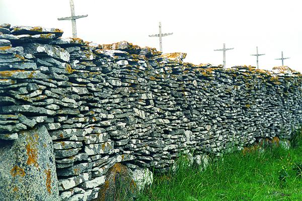 Holzkreuze hinter einer massiven Steinmauer aus vielen einzelnen flachen Steinen symbolisieren die Passion Christi