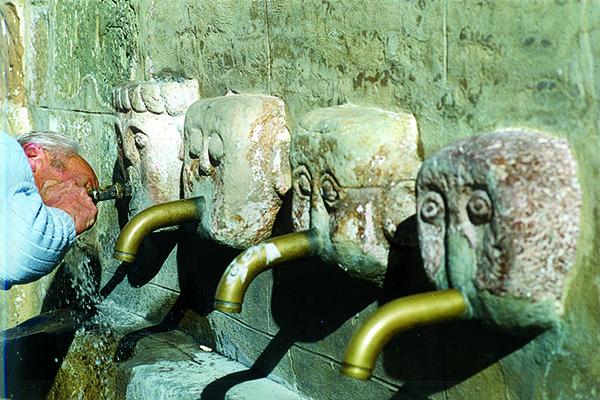 Ein Brunnen mit mehreren Steingesichtern und Wasserrohrenn als Münder symbolieren die Reformation